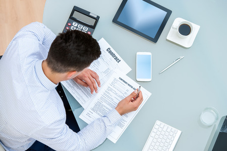 filling out: Close up portrait of young Office worker filling out contract documents.Top view of young man at table with pen and documents. Stock Photo
