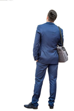 giving back: Full length portrait of young businessman standing in blue suit. Young man giving back to camera showing rear view.Isolated on white background.