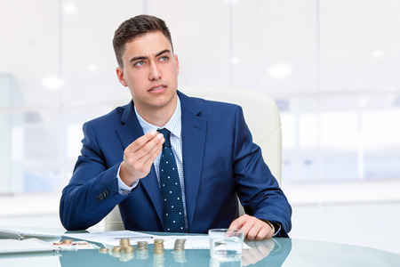 money matters: Close up portrait of young Businessman at desk holding money coins with wondering face expression. Young businessman in blue suit sitting at desk in office looking up. Stock Photo