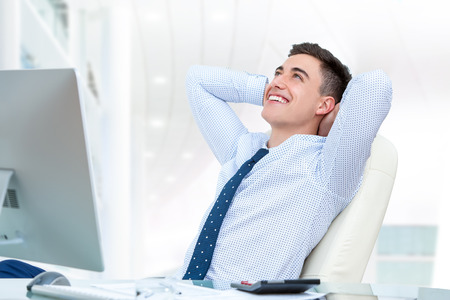 take time out: Close up portrait of young office worker relaxing in office. Young man sitting at desk with hands behind head and looking up. Stock Photo