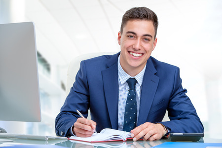 Close up portrait of young attractive businessman in blue suit at desk in office. Young man writing in agenda with pen.