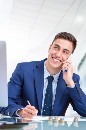 aside: Close up portrait of Handsome young businessman talking on smart phone in office. Young man at desk in front of computer and financial documents.
