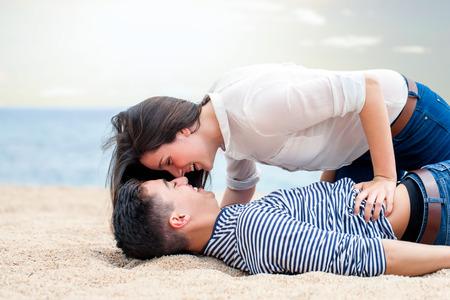 adolescente: Close up retrato de pareja de adolescentes amorosa jugando en la playa. Pares adolescentes reír y divertirse juntos.