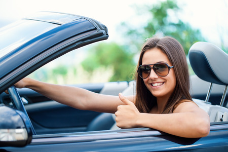 Close up portrait of Cute girl driving convertible doing thumbs up.
