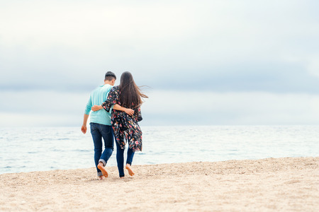 giving back: Young couple taking a walk on beach on cloudy day. Couple walking along seamless clouds and water giving back. Stock Photo