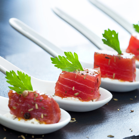 mouthful: Extreme close up of multiple appetizing tuna dices on white ceramic spoons.