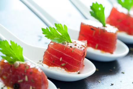 Macro close up of appetizing tuna morsel on ceramic spoons. Row of multiple tuna starters.