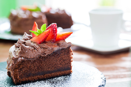 pastel de chocolate: Macro cerca de la rebanada de pastel apetitoso chocolate negro con fuera de foco en el fondo de café.