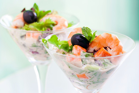 langoustine: Extreme close up of shrimp and crab cocktail salad served in transparent glasses. Stock Photo
