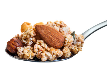 mouthful: Macro close up of Spoon with mouthful of crunchy muesli and nuts. Isolated on white background. Stock Photo