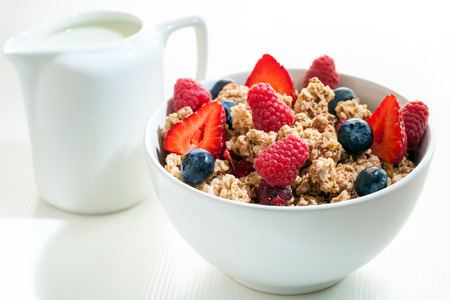 the milk jug: Macro close up of crunchy muesli with red fruit.White bowl with muesli and milk jug in background.