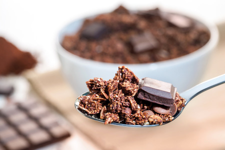 mouthful: Extreme close up of Spoon with crunchy chocolate muesli and bowl in background.