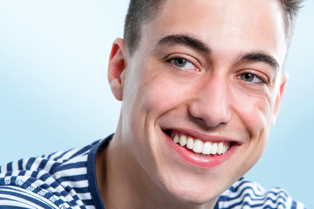 looking aside: Macro face portrait of Handsome young man with healthy teeth looking aside. Stock Photo