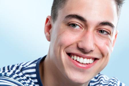 dientes sanos: Macro retrato de la cara del hombre joven y guapo con dientes sanos mirando a un lado.