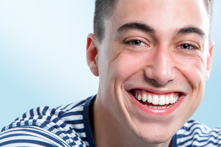 toothy smile: Extreme close up face shot of Young man with charming and healthy toothy smile.
