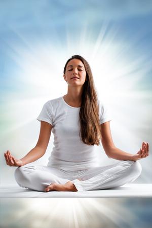 mujer meditando: Close up retrato de mujer joven y atractiva meditando con los ojos cerrados. Vista frontal de la mujer vestida de blanco en posición de yoga con rayo de luz en el fondo.