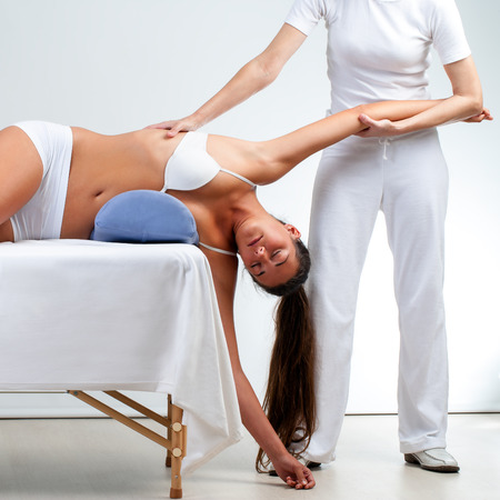 alternative practitioner: Osteopath stretching woman's shoulder on massage bed at session. Stock Photo