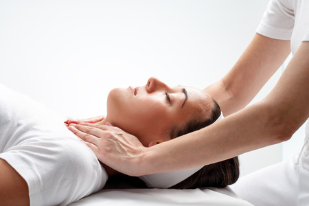 healing touch: Close up portrait of young woman at reiki session.Therapist touching woman's neck wit hands. Stock Photo