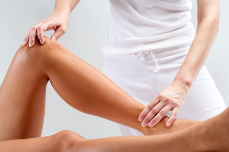 Close up of therapist doing manipulative healing treatment on female legs.