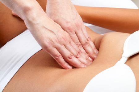 Macro Gros plan des mains du thérapeute faisant massage viscérale abdomen de la femelle.