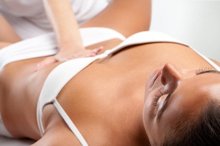 visceral: Close up of young woman receiving osteopathic visceral massage with therapist hand pressing on stomach. Stock Photo
