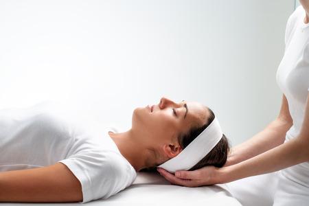 física: Close up retrato de mujer joven que se relaja con los ojos cerrados en session.Girls reiki cabeza apoyada en las manos del terapeuta. Foto de archivo