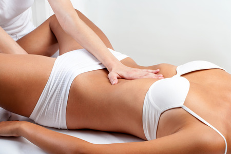 Close up of osteopath doing abdominal massage on woman. Stock Photo