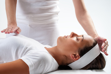 Close up of chiropractor's hands doing reiki on young woman.One hand on head and one hand on chest.