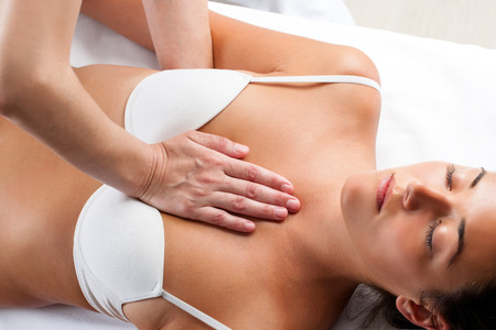 Close up of physiotherapist doing manipulative massage on young woman's chest.