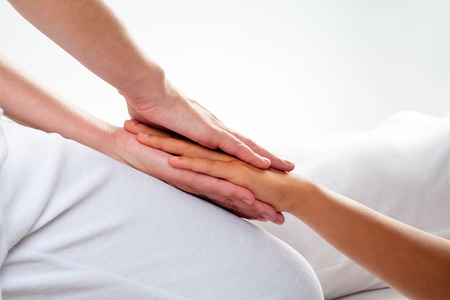 Close up of chiropractor doing reiki treatment on girls hand. Stock Photo