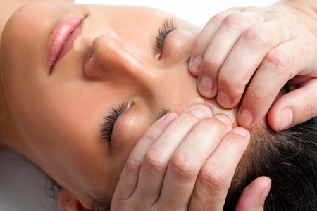 osteopathy: Macro close up face shot of young woman receiving massage. Therapist hand doing manipulative treatment on forehead.