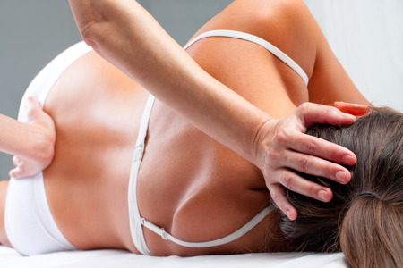 Close up of osteopath doing spinal column rehabilitation exercise on young woman.