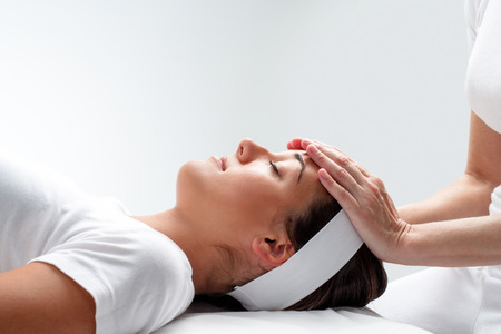 osteopath: Close up portrait of young woman relaxing at reiki session.Therapist touching girls head with hands.