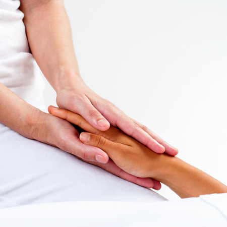 healing practitioners: Macro close up of therapist hands holding woman's hand.Healing treatment at reiki session. Stock Photo