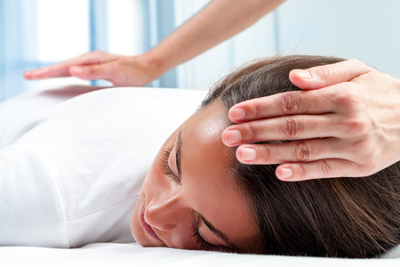 alternative healing: Therapists hands doing reiki therapy on girl. One hand on head and one hand on back. Stock Photo