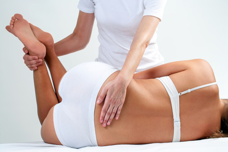Therapist doing lower back massage on woman.Osteopath rotating woman's legs. Stock Photo