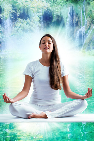 Close up portrait of attractive woman dressed in white meditating. Young girl sitting i yoga position at mystic blue lagoon with waterfalls in background.