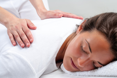 treatments: Close up portrait of young woman laying facing head down.Therapist doing reiki treatment with hands on back. Stock Photo