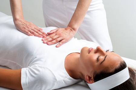 física: Cierre de quiropráctico presionando con las manos en el pecho mujer en la sesión de reiki.