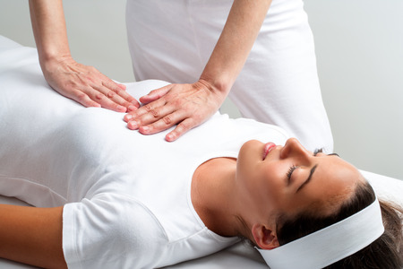 physical test: Close up of chiropractor pressing with hands on womans chest at reiki session. Stock Photo