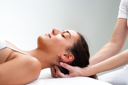 testa: Cierre de quiropr�ctico presionando posterior de la mujer con la cabeza. Terapeuta haciendo la curaci�n de masaje con los dedos en la parte posterior del cuello. Foto de archivo