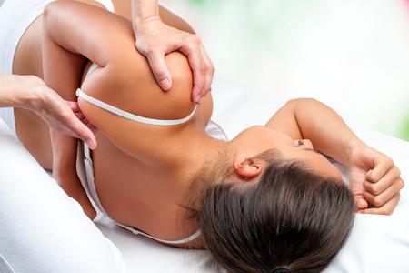 fisioterapia: Cierre de vista superior del oste�pata haciendo curaci�n tratamiento sobre el om�plato femenina. Foto de archivo