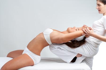 dolor espalda: Cerca de la fisioterapeuta que hace el masaje de estiramiento manipuladora en la mujer joven. Mujer descansando con la parte posterior de la rodilla terapeuta. Foto de archivo