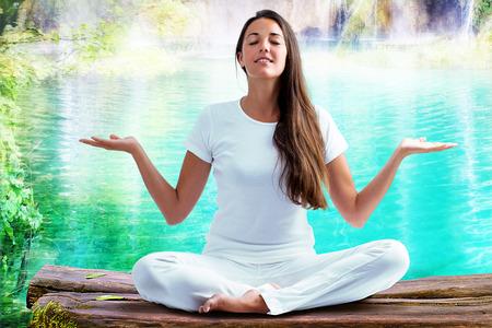 Close up portrait de jolie femme vêtue de blanc, assis en position sur bûche de bois méditant au lagon bleu. Jeune fille à main levée faisant du yoga.