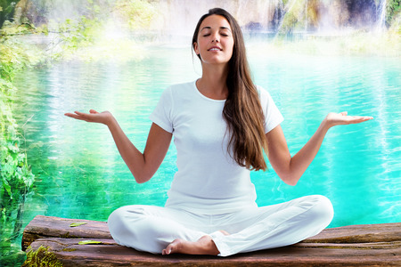 spirituality therapy: Close up portrait of attractive woman dressed in white sitting in meditating position on wooden log at blue lagoon. Young girl raising hands doing yoga. Stock Photo