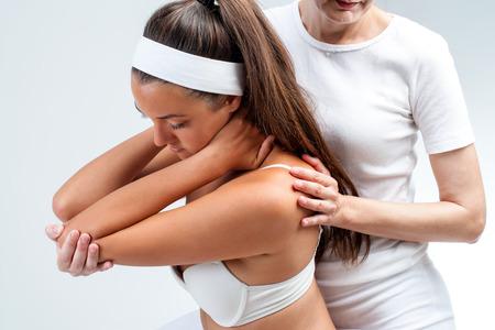 Close up de faire physiothérapeute rotation massage des épaules sur le jeune femme.