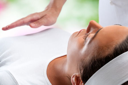 Close up portrait of young woman relaxing at reiki session with therapist hand in background. Stock Photo