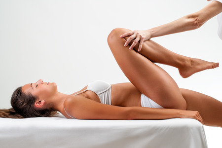 Close up of Osteopath doing healing massage on young woman.Full length portrait of girl laying on back and therapist applying pressure on womans leg.