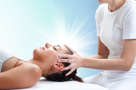 energy healing: Close up portrait of therapist doing healing treatment on young woman.Therapist touching head with light glow in background. Stock Photo