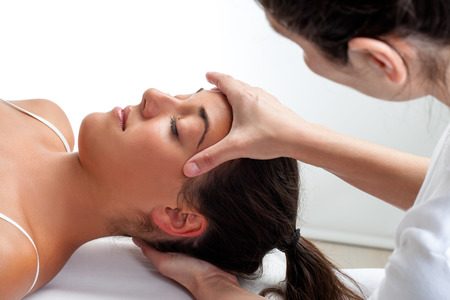 osteopathy: Close up of osteopath doing healing treatment on womans head. Hands doing massage on front and back of head.
